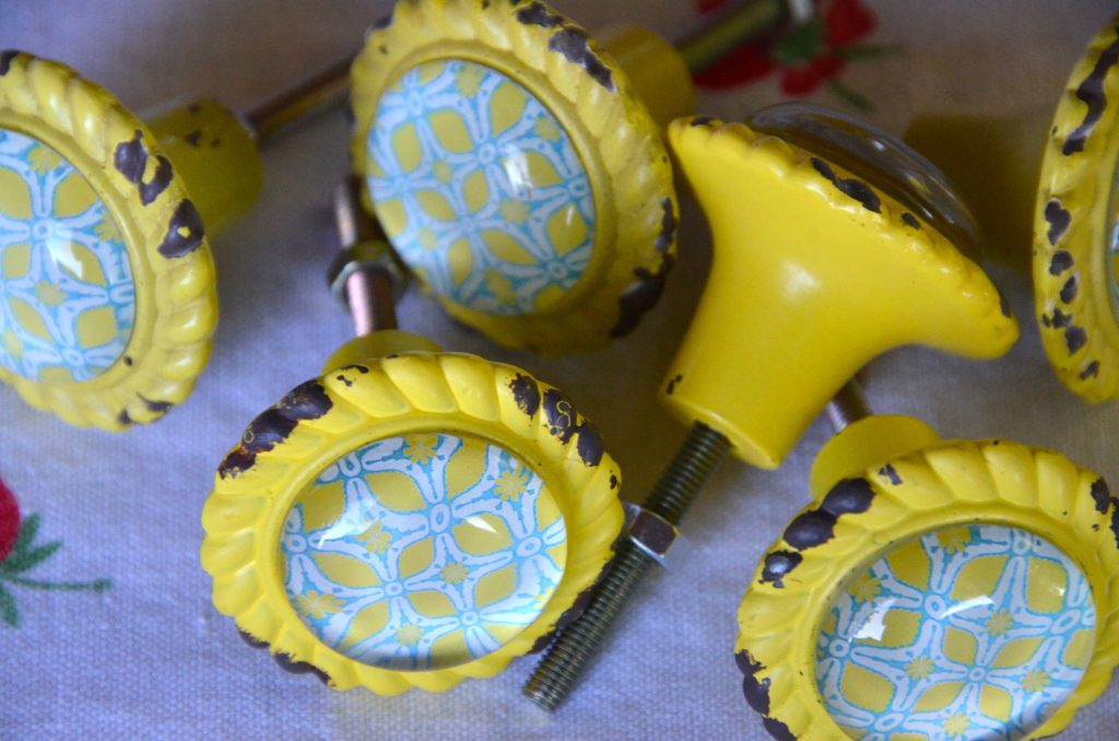 Yellow and teal knobs have a rustic and farmhouse look