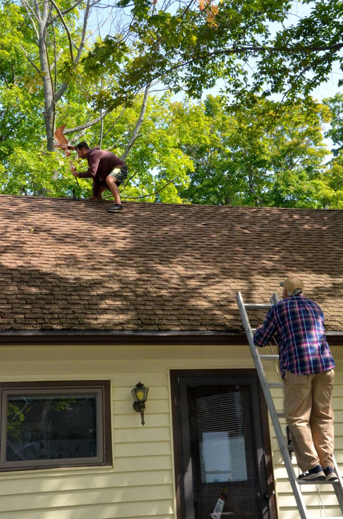 Tom and his dad installing weathervane