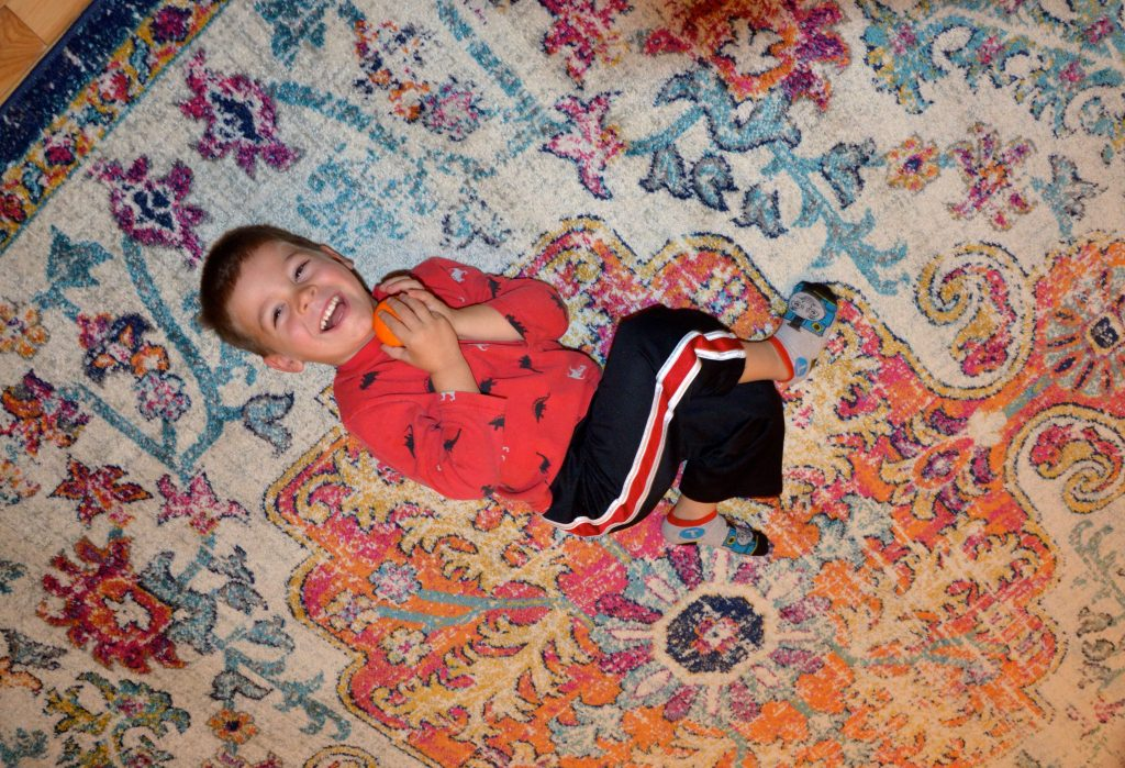 three year old laughing on a rug