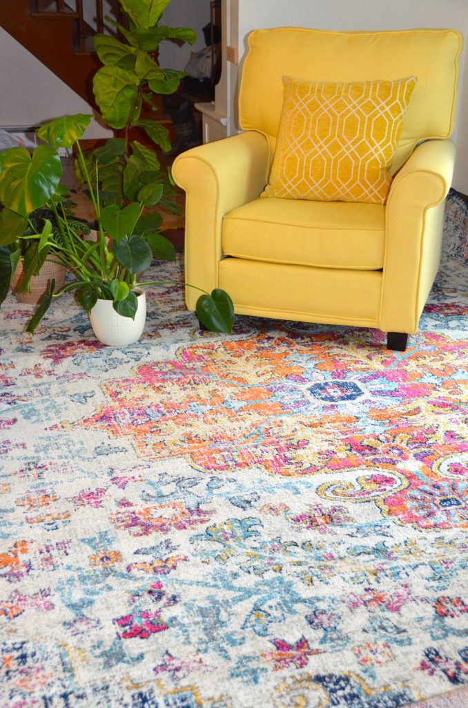 Multi-colored rug with yellow chair and plant.