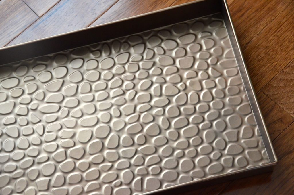 Versatile boot tray is pretty with pebbles design